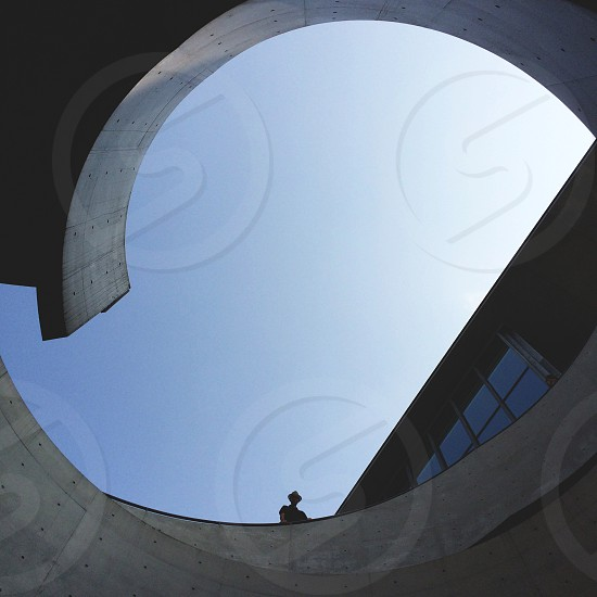person wearing t-shirt and fedora hat standing on top of grey concrete spiral building under blue and white sky photo