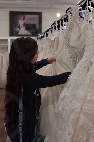 woman choosing white wedding gown photo