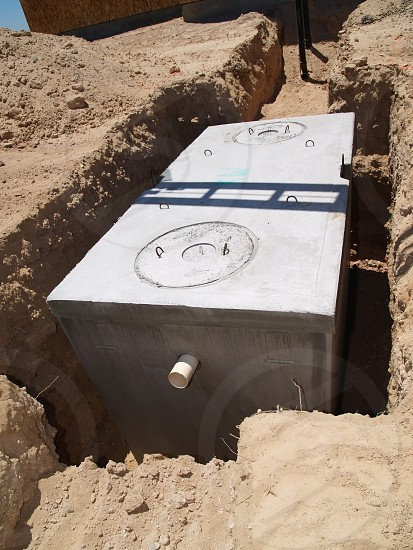 A brand new septic tank ready to be connected to a newly constructed home and then covered with soil to hide it from view. photo