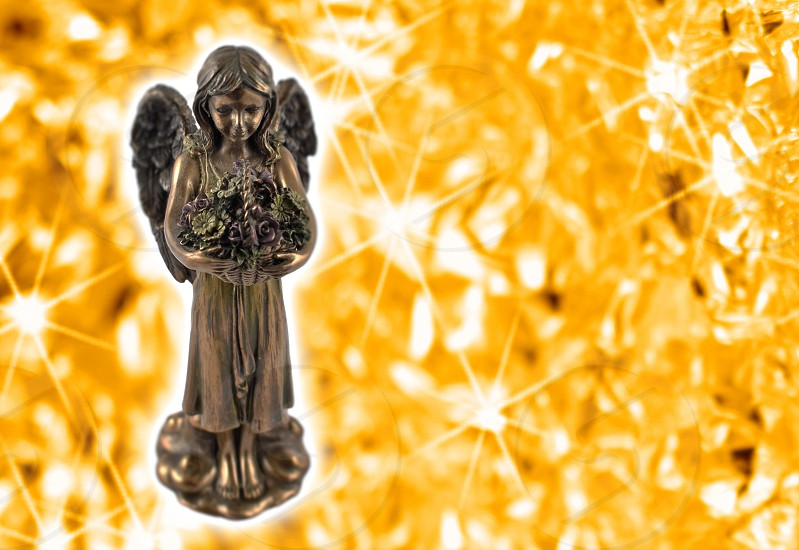 Angel statue. Angel on a starry background. Angel figurine on a golden background with copy space for text photo