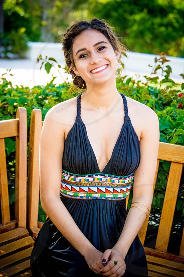 woman in black pleated halter deep v neck maxi dress sitting on brown wooden windsor chair photo