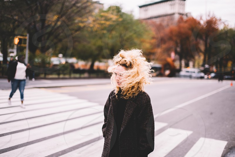 blonde curly hair woman wearing a black jacket walking across a crosswalk with a woman walking in the distance photo