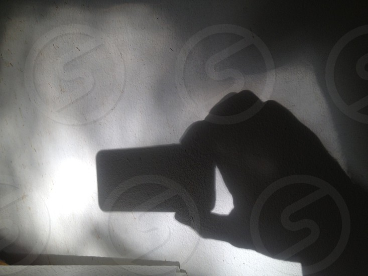 A shadow of a hand holding an iPhone taking a picture of itself :) photo