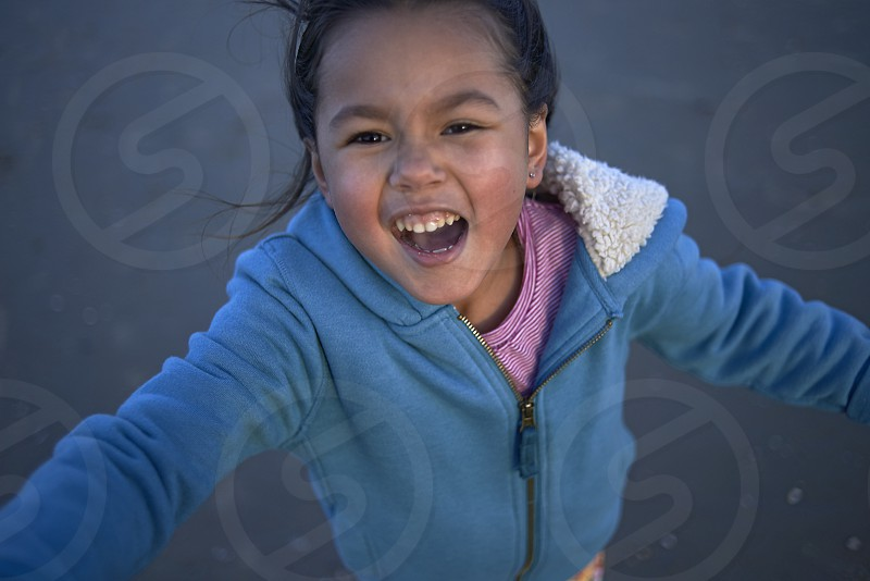 Cute little girl wearing a hooded sweater running on the beach and happily smiling into camera photo