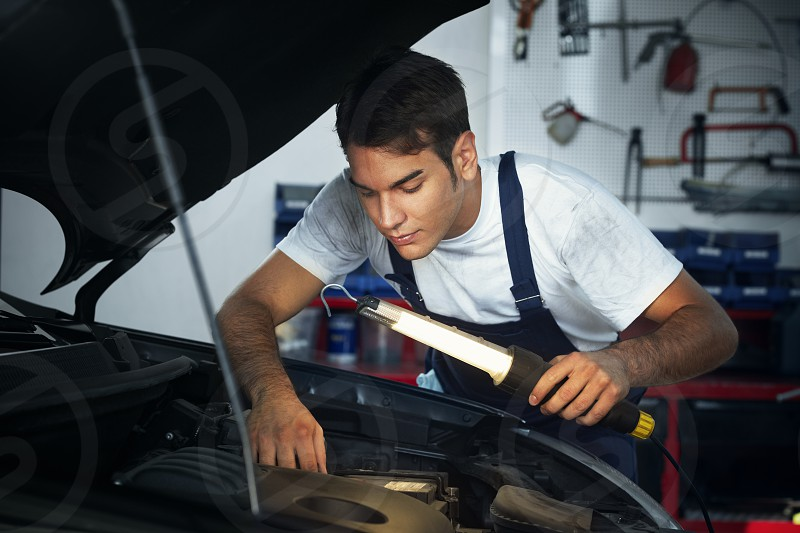 mechanic; man; car; working; repairing; engine; bonnet; people; one person; male; Caucasian; young; adult; young man; mid adult; 30s; waist up; serious; concentration; overalls; side view; looking; seeking; examining; holding; hood; lamp; light; lighting; indoors; garage; repair station; transportation; transport; vehicle; auto; automobile; motor vehicle; broken car; repair; car repair; auto repair shop; manual worker; occupation; fixing; expertise; skill; determination; work; service photo