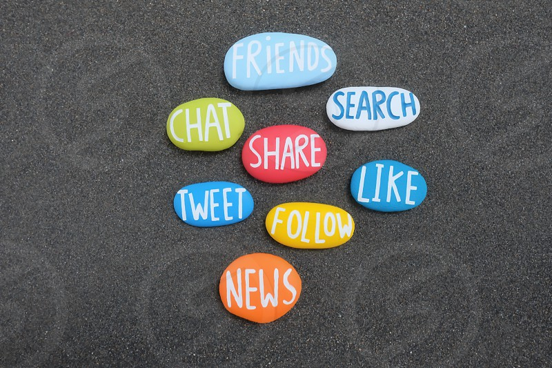 Social words composed with carved and multi colored stones over black volcanic sand photo