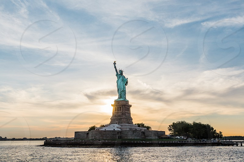 The setting sun behind Lady Liberty in New York City  photo