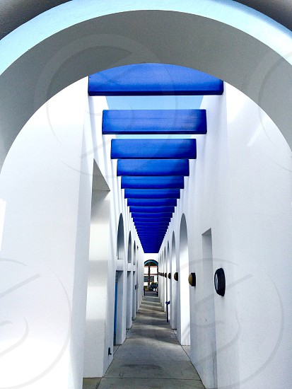 Walkway outdoors architecture blue beams white walls arch pattern converging lines photo