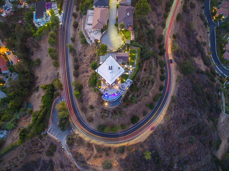 aerial photography of a winding road on a hillside around a cul de sac of homes photo