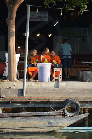 3 monks sitting on bench  photo