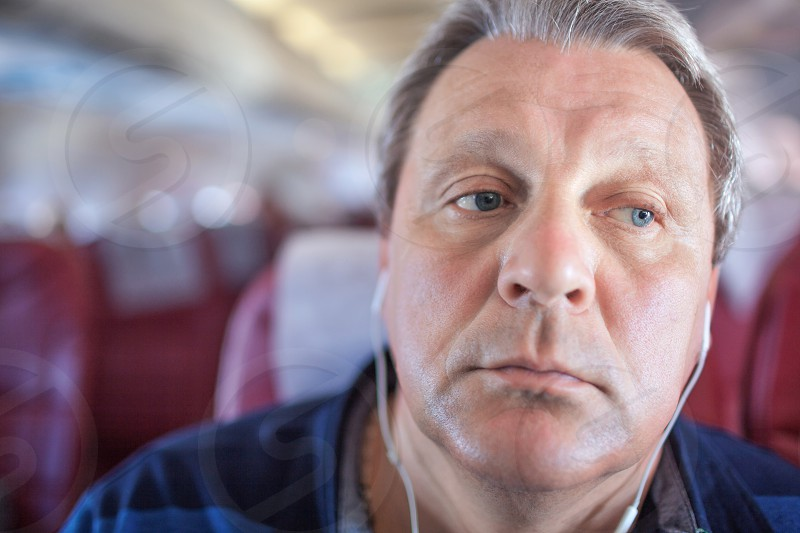 Close-up shot of mature man listening to music in headphones during traveling by plane. He looking distracted photo