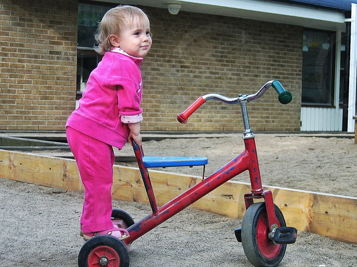 girl playing with trike toy photo