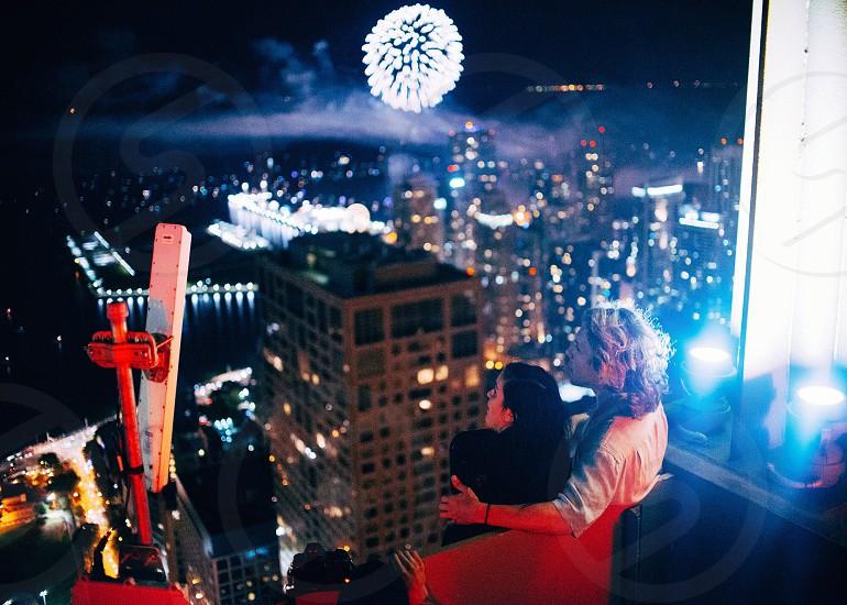 woman in black shirt beside man in white long sleeve shirt watching fireworks near window photo
