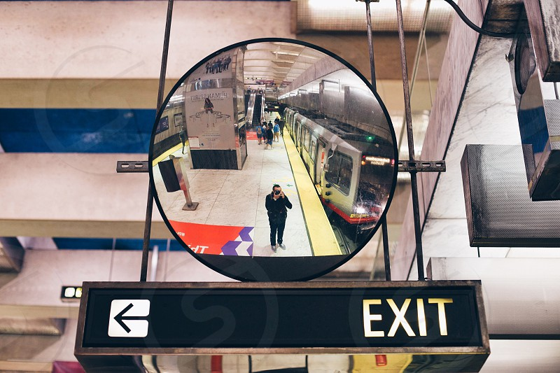 view of a round mirror and an exit sign photo