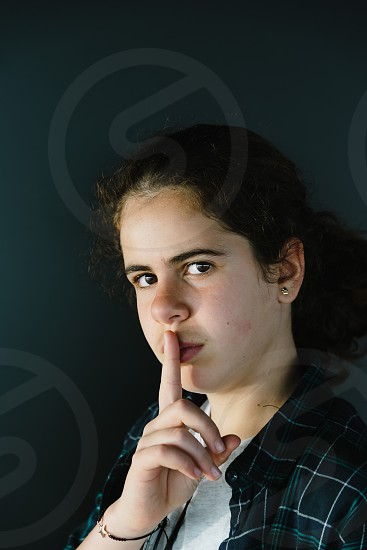 Headshot portrait of defiant teenager with finger on lips making silence gesture. Concept photo