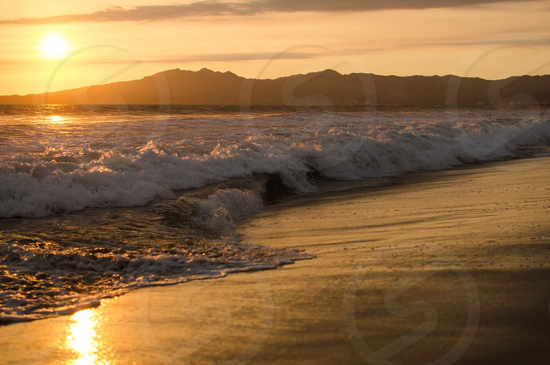 Beach and waves at sunset with mountain background. photo
