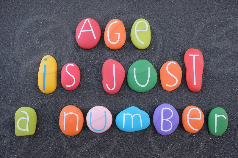 Age is just a number creative phrase for a happy birthday with colored stones over black volcanic sand photo