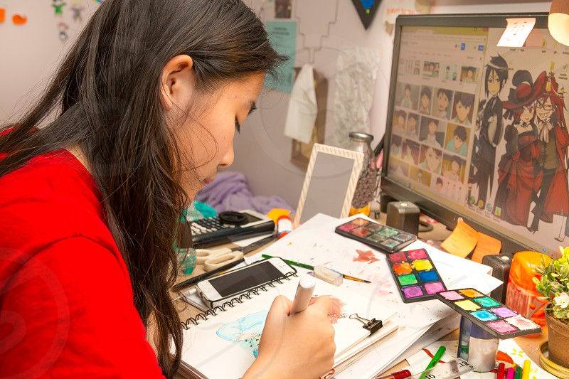 girl in red shirt making artwork on white note during daytime photo