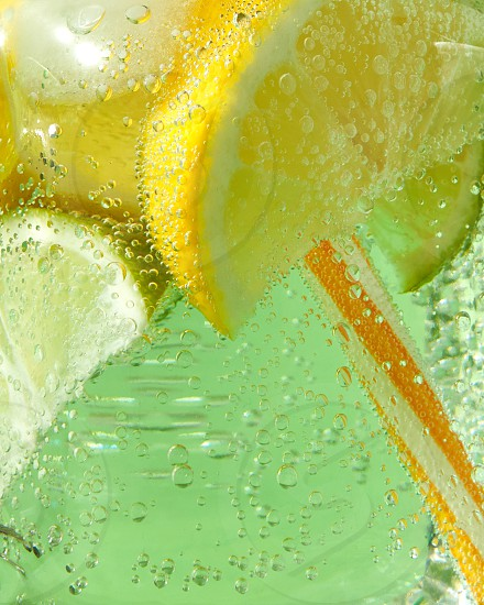 A macro shot of a glass with a cold refreshing lemonade with ice pieces of lime lemon and mint leaves plastic straws on a green background. Bubbles of air in a glass jar. photo