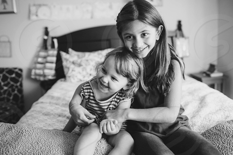 2 girls sitting on bed smiling in grayscale photography photo