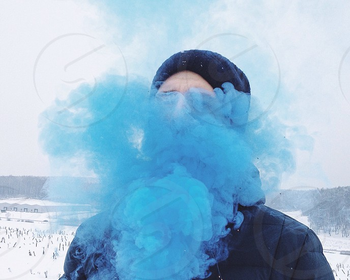man wearing a hooded down filled jacket behind blue smoke standing in white snow photo