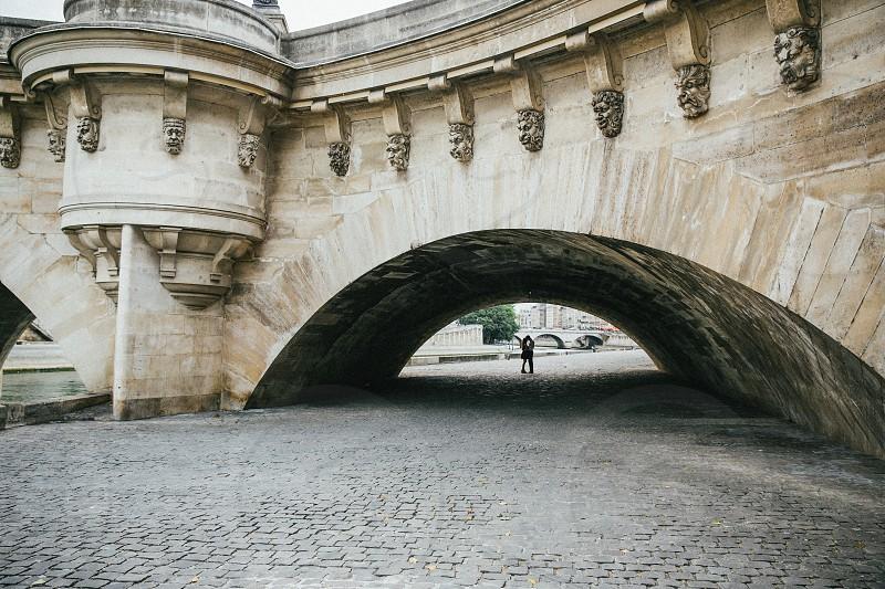 man walking below brown concrete bridge photo