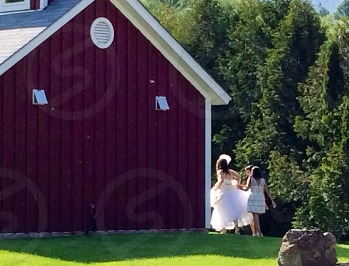 ladies walking on the side of a red barn photo