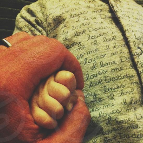 man holding baby's hand photo