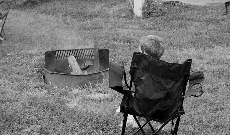 Camp camping boy kid child chair sit sitting black white nature outdoors outside fire hot Summer  photo