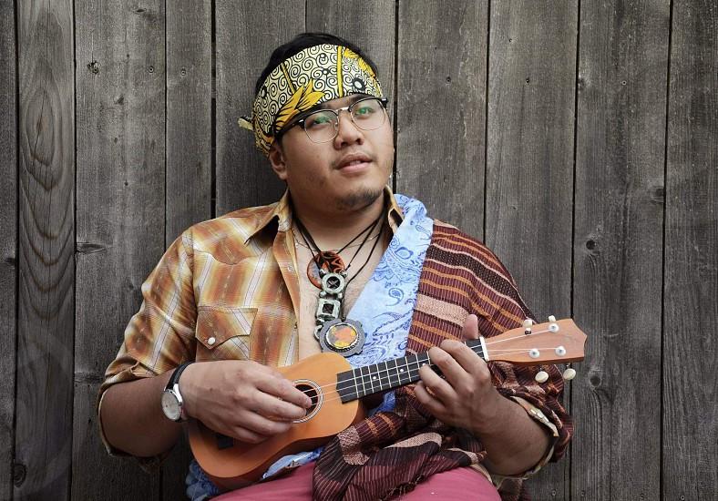Hippie guy playing ukelele photo