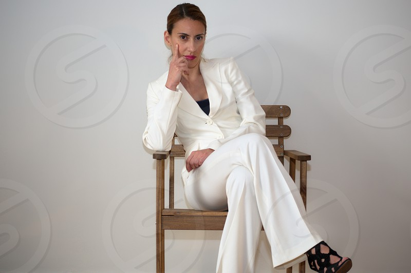 Woman in suit sitting on a wooden chair photo