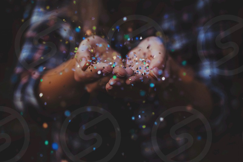low light and time lapse photography of woman throwing multicolored glitters photo