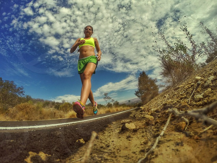 woman wearing green sport brassiere and shorts running in middle of road under white clouds photo