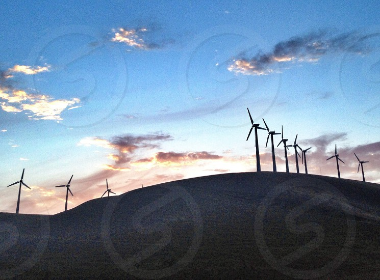 silhouette of windmills on a hill photo