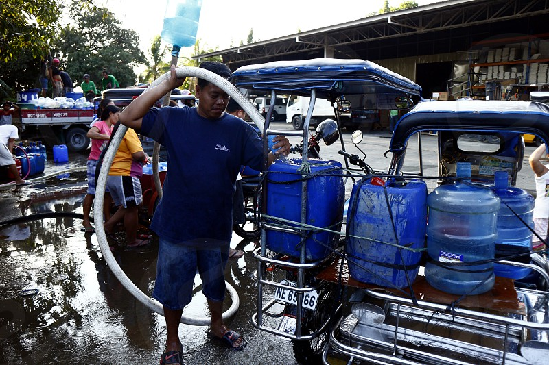 ANTIPOLO CITY PHILIPPINES - MARCH 14 2019: Residents fill their containers with deep well water when a service interruption lasted for days causing water shortage. photo