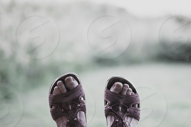 Feet of person lying on the grass and wearing sandals. Blurred bright natural background with space for copy.Relaxation concept.POV image. photo
