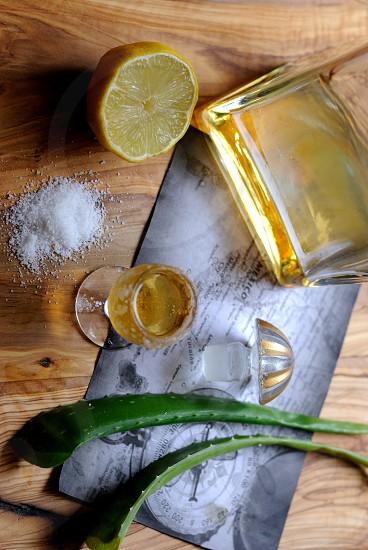 2 aloe vera leaf and sliced lemon placed near glass bottle and flute glass with salt photo