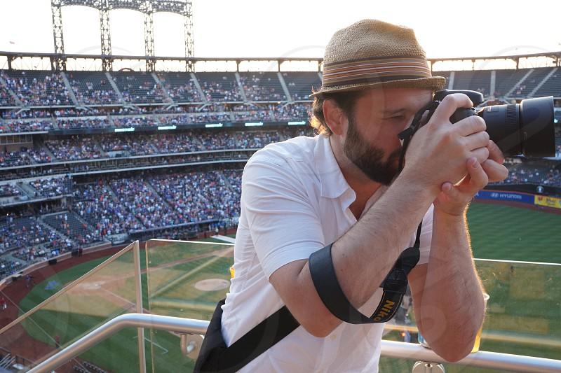man taking a photo in a stadium photo