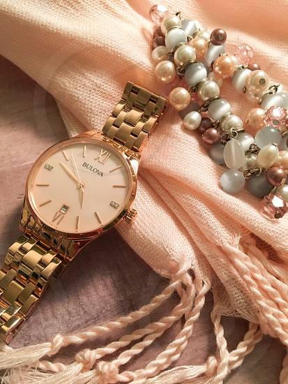 silver link round bulova analog watch beside pink and white pearl bracelet photo