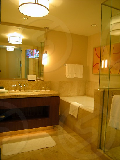 Beige hotel bathroom with deep soaking tub rainshower and TV in mirror photo