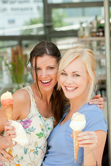 Two women eating ice cream cones outside photo