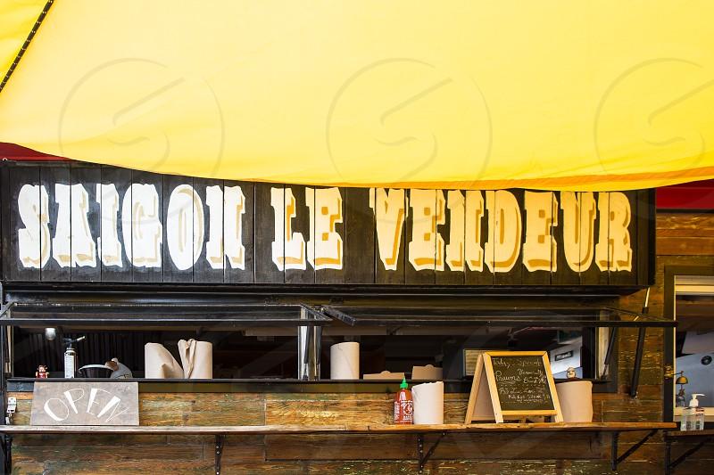 saigon le vendeur wooden signage on restaurant during daytime photo