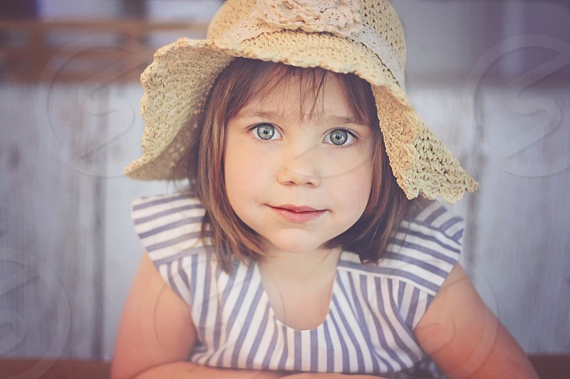 girl in grey white striped short sleeve shirt with straw bendable sun hat photo