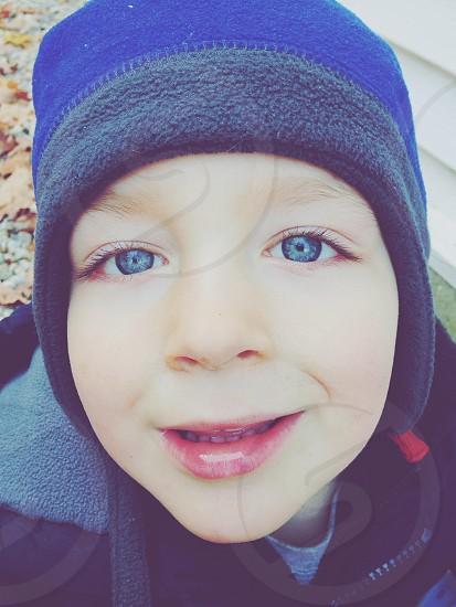 Blue-eyed smiling boy in winter clothing photo