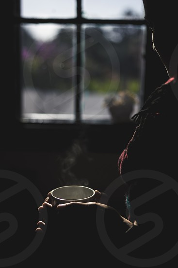 young woman standing in front of the window with a cup of hot tea photo