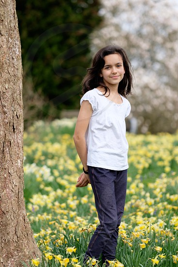 Portrait of a young dark haired girl with a neutral expression on her face in a white top and dark blue leggings standing next to a tree in a garden with yellow daffodil flowers behind her out of focus photo