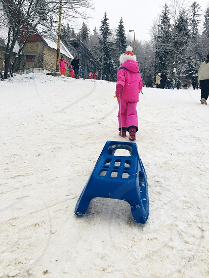Winter child playing snow snowing sledge photo