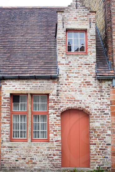 Painted door in a color of the year 2019 Living Coral Pantone on old European brick house of Bruges Belgium. photo