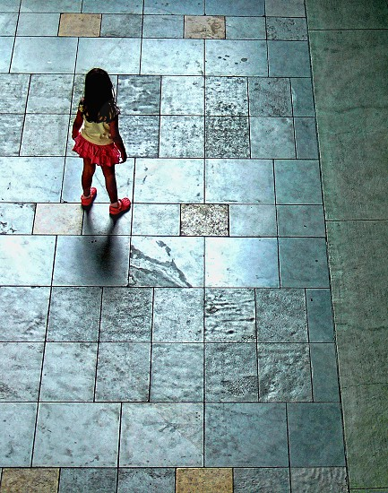 Seen from above and behind a little girl stands alone on a tile floor looking lost. photo