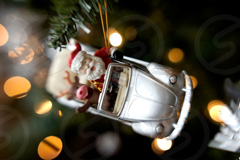 Christmas ornament on a tree featuring Santa and a reindeer riding in a convertible car photo